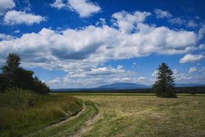 höstlandskap med moln och klippt gräs foto