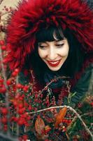 porträtt av en vacker ung brunettkvinna i rött med ett leende och huva med rött hår i skogen bakom en buske med röda bär foto