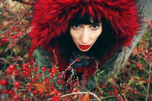 porträtt av en vacker ung brunettkvinna i rött med huva med rött hår i skogen bakom en buske med röda bär foto