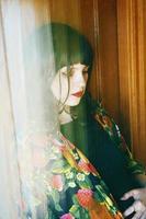 konstnärligt porträtt med asiatisk inspiration av en ung kvinna som ses genom ett fönster foto