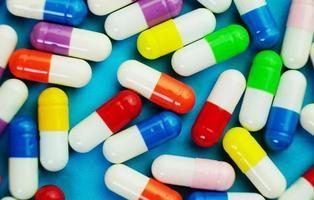 ett detaljerat makro av piller och kapslar med blå bakgrund foto