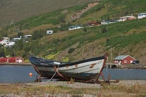 gammal vintage båt med en liten stad i eskifjodur ligger i östra Island i bakgrunden foto