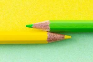 färgpennor på gula och gröna papper ordnade horisontellt foto
