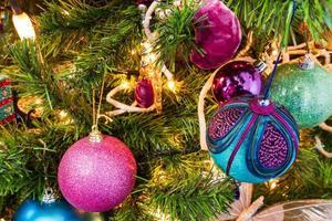 julgran med dekorativa bollar och ljusljus foto