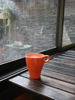 mjölk i orange mugg på träbord i kafé foto