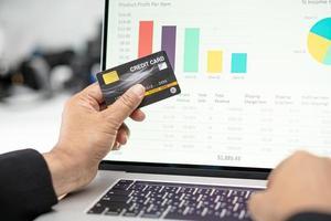 asiatisk revisor som arbetar beräknar och analyserar rapportprojektbokföring med anteckningsbok och kreditkort i modernt kontor foto