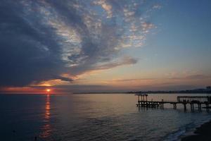 dramatisk solnedgång med mörka moln över det lugna havet foto