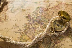 gammal kompass och rep på vintage karta foto