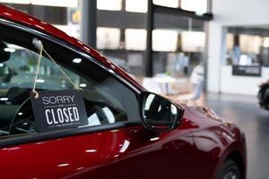 röd bil i återförsäljarförsäljning, stängd för låsning av coronavirus foto