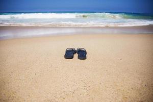 sommar tofflor på stranden foto