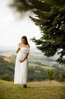 ung gravid kvinna i skogen foto
