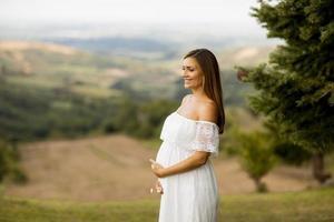 ung gravid kvinna på fältet foto