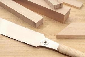 grupp av diverse trämaterial och en japansk handsåg snickeri timmermaterial klippt eller träbearbetning koncept foto