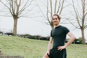 en ung atletisk man som ler mot kameran medan han tränar i parken med kopieringsutrymme och hörlurar foto