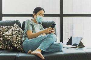 kvinna som bär skyddande mask sitter på soffan med smartphone i karantän foto