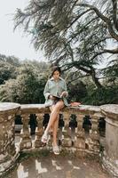 ung kvinna som sitter på en gammal byggnad som läser en bok under en solig dag med kopia utrymme livsstil och lycka koncept foto