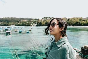 ung kvinna i en båtdocka som ler under en solig dag medan du använder solglasögon stranddag foto