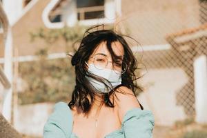 ung kvinna som använder ett maskporträtt under en sommardag med kopieringsutrymme foto