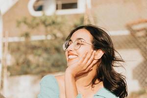 ung kvinna med glasögon som ler mot kameran under en super solig dag med kopia utrymme livsstil koncept lycklig dag foto