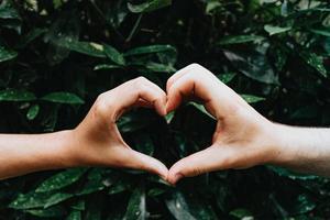 unga händer som gör en hjärtsymbol foto