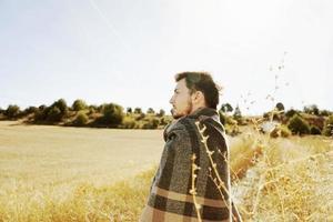 sida av en ställning ung man njuter i lugn av morgonen höstsolen i en väg av ett gult fält med bakgrundsbelysningen från den blå himlen foto