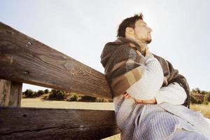 sidoansikte av en ung man med slutna ögon njuter i lugn på morgonen höstsolen i ett gult fält med bakgrundsbelysningen från den blå himlen foto