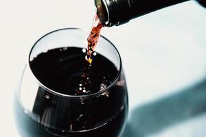 hälla vin i glaset foto