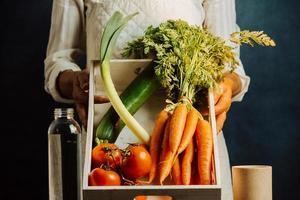 kvinna som håller en vit låda med grönsaker foto