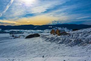 snöigt landskap mot solnedgången foto
