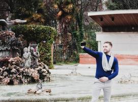 ung man tar en bild med sin mobiltelefon i parken foto