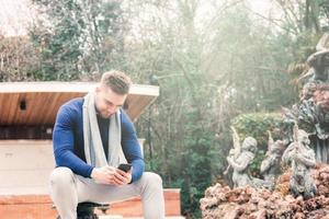 ung man sitter i fontänen i en park och tittar på sin mobiltelefon foto