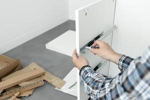 man montera möbler med en skruvmejsel foto