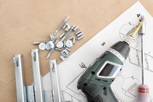 ovanifrån av en sladdlös skruvmejsel, lådreglage, skruvar och tillbehör för montering av möbler foto