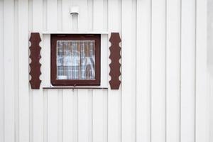 yttre nära träfönster med gardin på timmerväggshuset foto