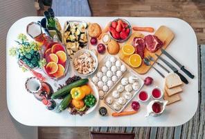 rå mat nötkött ägg med hälsosam mat grönsaker frukt beredd matlagning på bordet på bordet foto