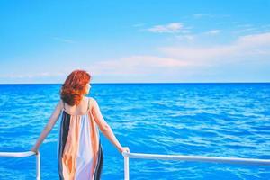 bakom flicka på pir med havsbakgrund foto