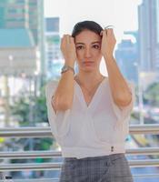 stående av en vacker asiatisk kvinna som står i en stadsbyggnad som ler lyckligt urban livsstil foto