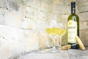inställning av georgiskt vitt vin mildiani med kork och två fulla glas i ljus tegelvägg bakgrund foto