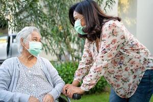 hjälp asiatisk senior eller äldre gammal damkvinna på rullstol och bär ansiktsmask för att skydda säkerhetsinfektion covid 19 coronavirus i park foto
