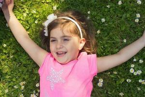 liten flicka som lägger i gräset foto