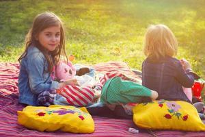två små flickor som har picknick i trädgården foto