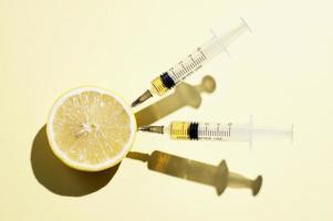 en torkad apelsin och två medicinska sprutor med juice på blå bakgrund foto