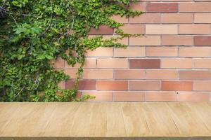 trägolv med bakgrund av röd tegelvägg och grön växt foto