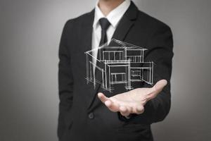 affärsman som visar en modell av huset foto