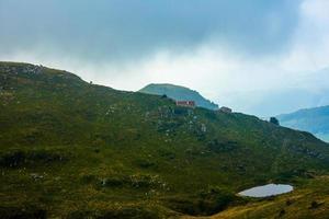 alpin betesmark med sjö och ladugård foto