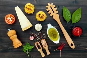 pastan på svart träbakgrund gul italiensk pasta med ingredienser italiensk mat och menykoncept foto