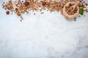 rostade kaffebönor med skopor på vit betongbakgrund foto