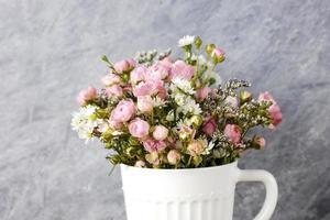 mini rosa rosblommor i vit kopp foto
