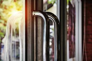 dörrhandtag i rostfritt stål med solljus foto