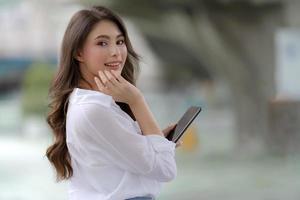porträtt av ung kvinna med smiley ansikte med en telefon promenader i en stad foto